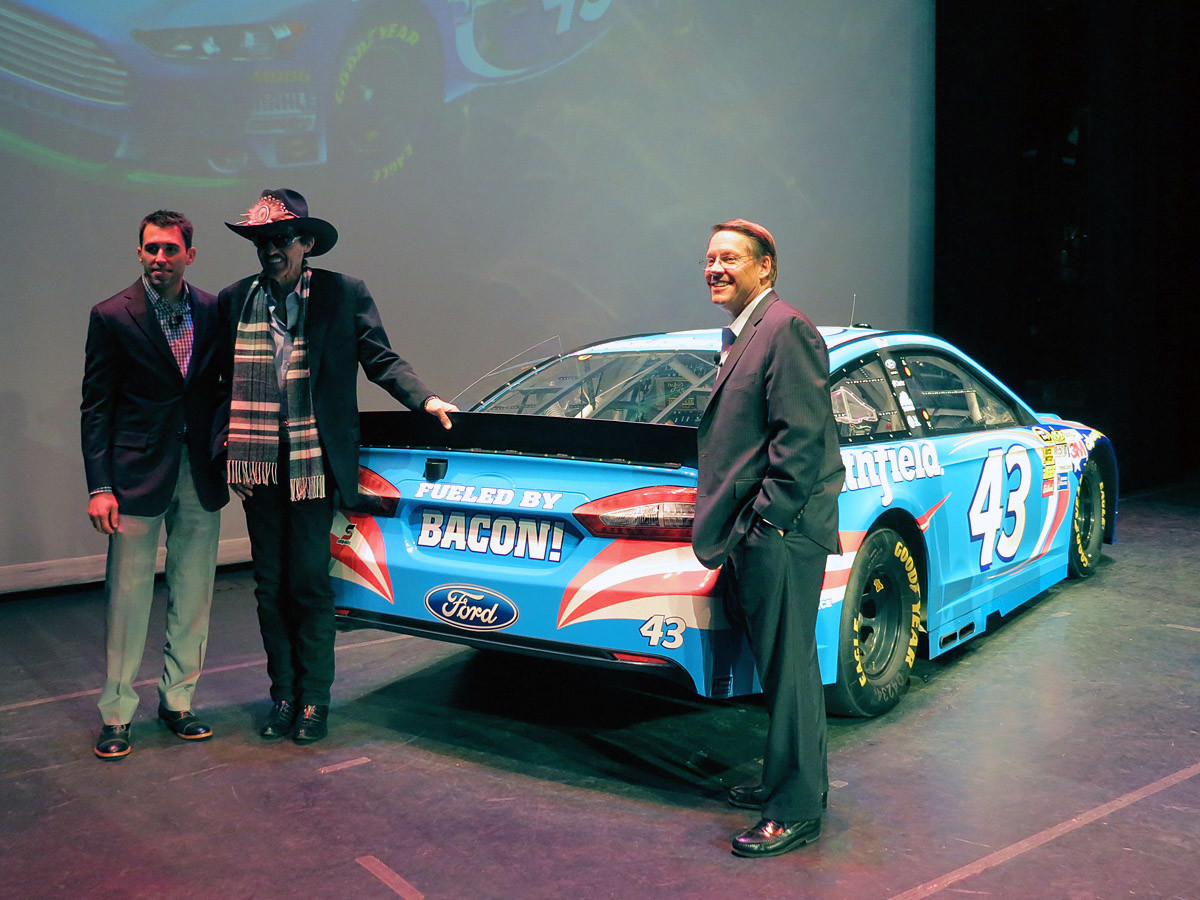 (Left to Right) NASCAR Sprint Cup Series driver Aric Almirola, team owner Richard Petty, and Smithfield CEO Larry Pope pose on stage with the 2014 #43 Smithfield Ford Fusion. January 15th, 2014.