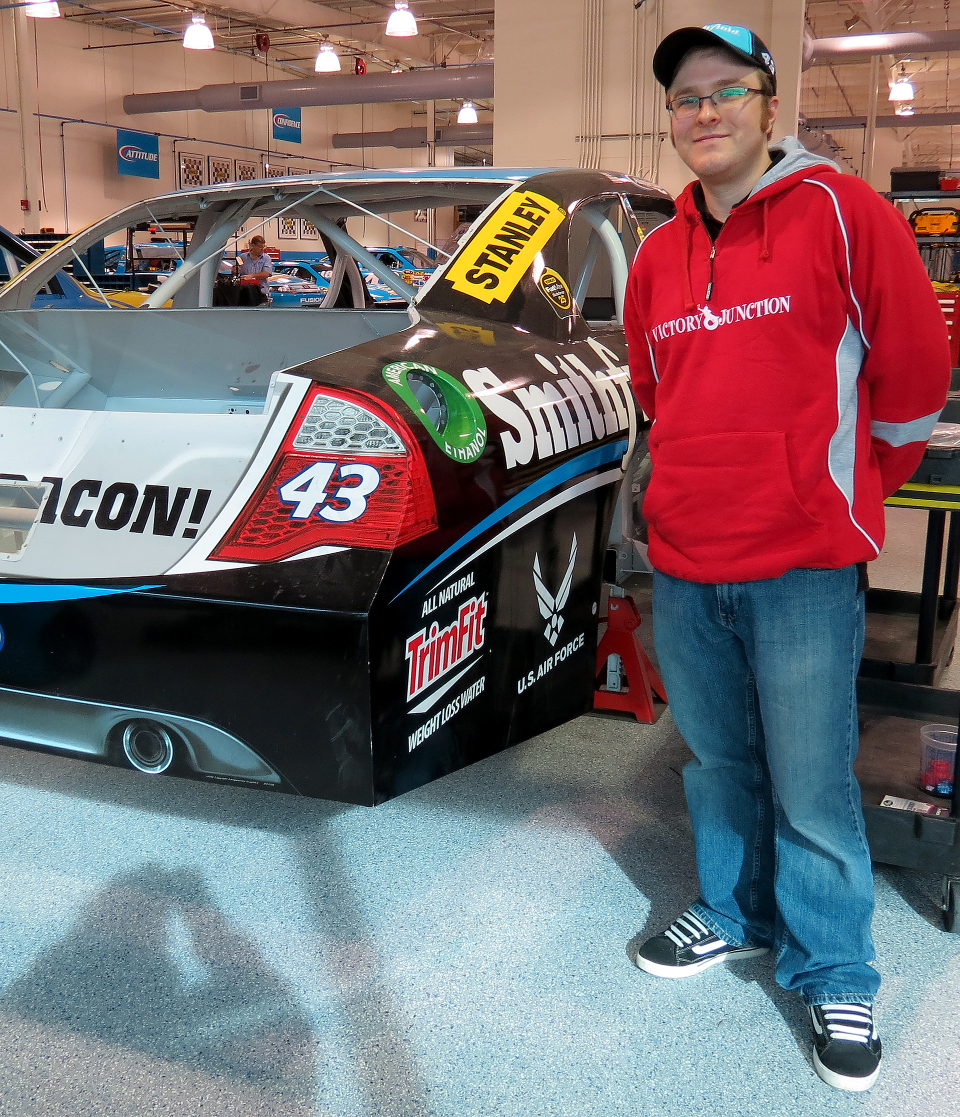 Standing with the previously raced Watkins Glen car as it sits in the Richard Petty Motorsports race shop