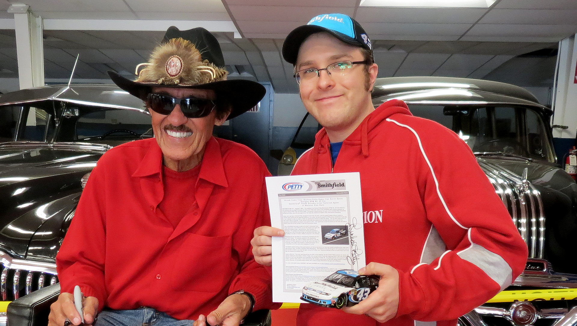 """The King"" Richard Petty signs the Smithfield press release announcing the new car design for 2012 and my custom diecast car at his Petty's Garage shop in Level Cross, NC"