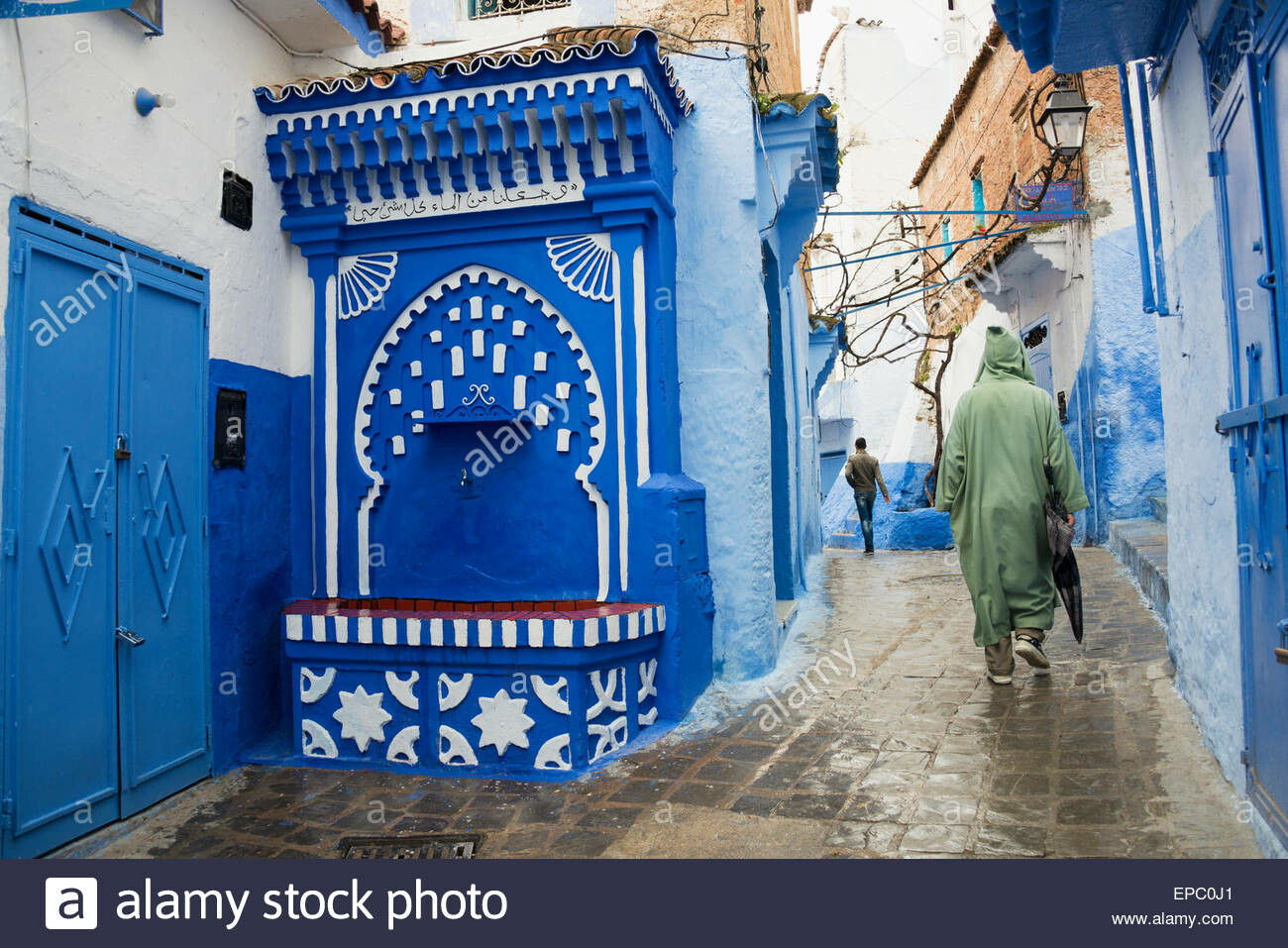 Claire bian water fountain with islamic arch in street scene chefchaouen morocco epc0j1